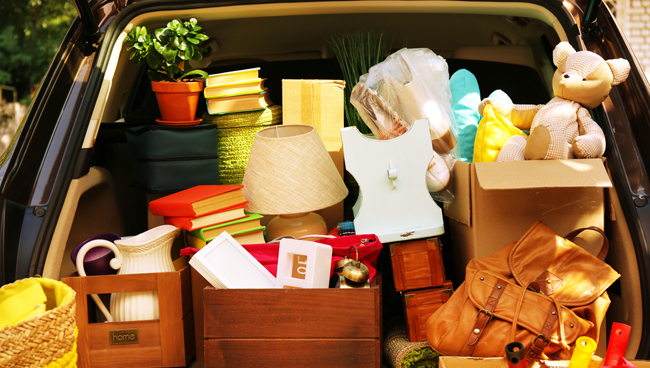 Car boot filled with items for storage, boxes, toys, bags and lamps